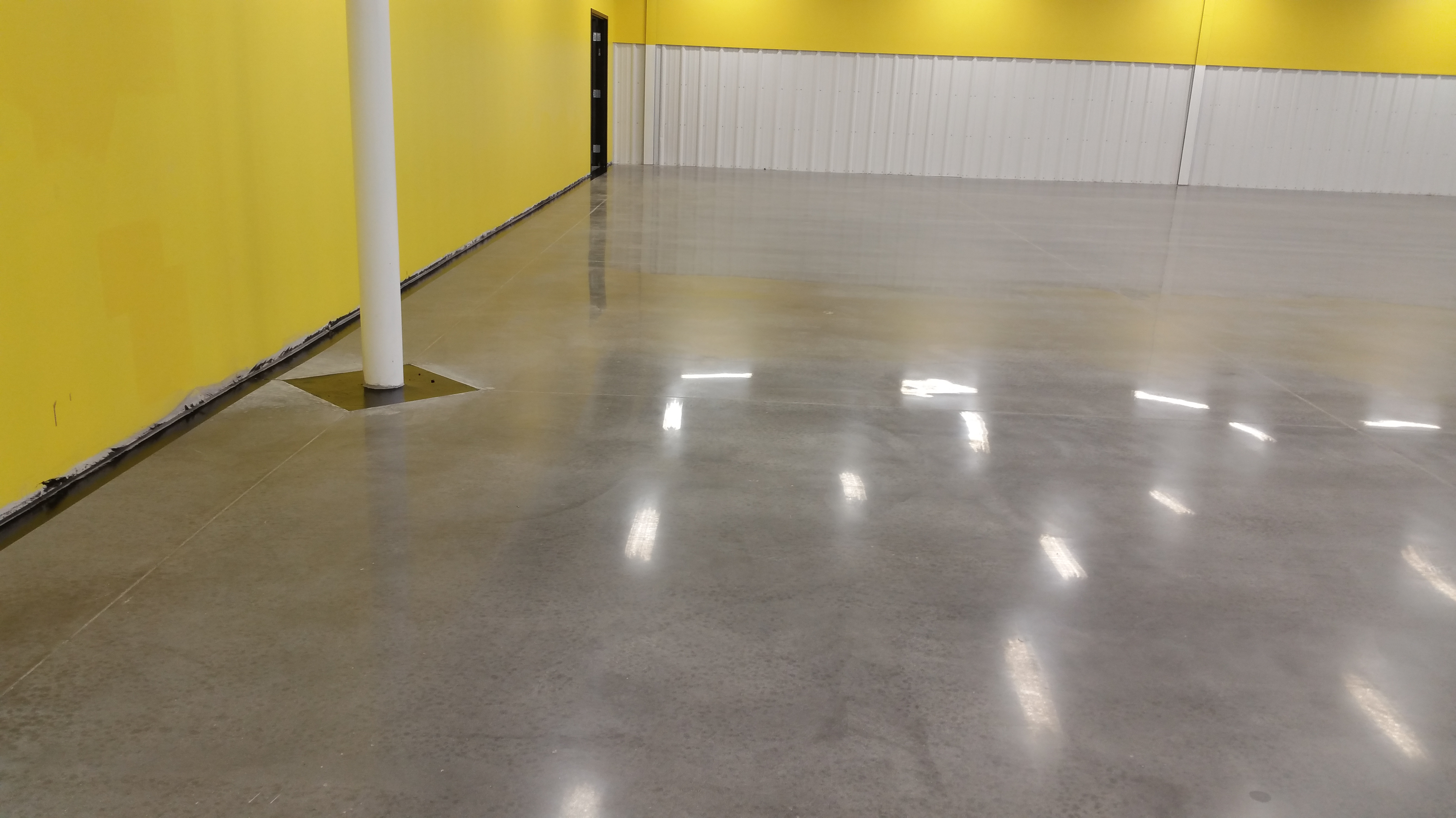 Overhead lights reflect off a polished cement floor.