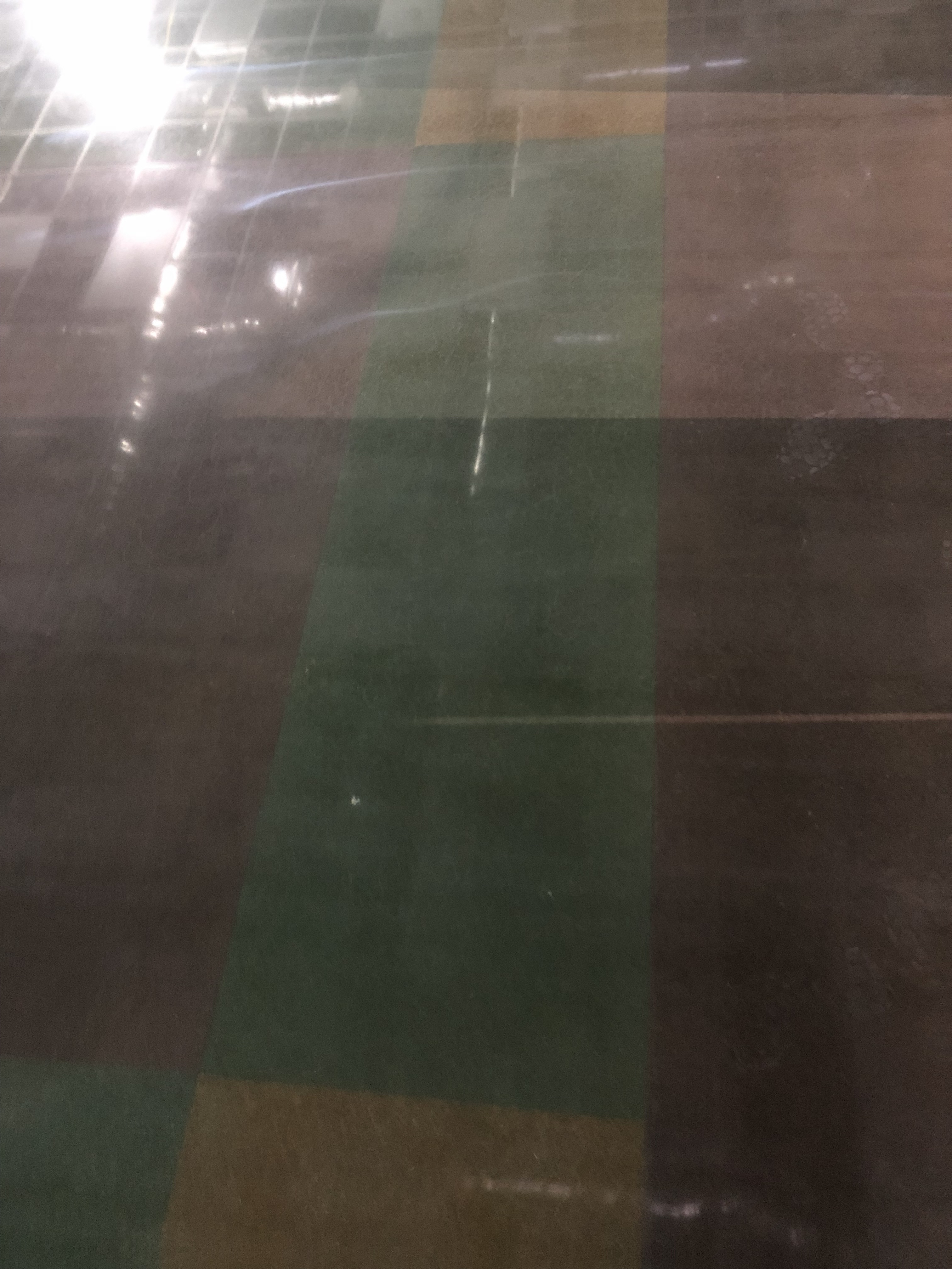 A polished concrete floor demonstrating a red, green, and yellow square pattern.